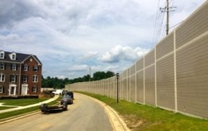 Wide view of gracefully-curving noise barrier wall with townhomes