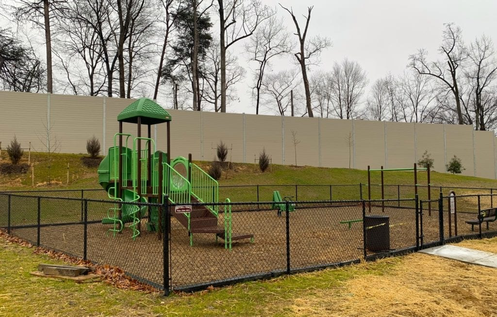 Playground in front of residential noise barrier wall
